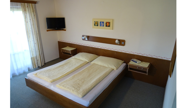 Doppelbett, Nachtkästchen, seitlich eine Balkontür