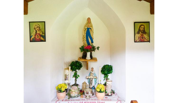 seitlich Heiligenbilder, im Hintergrund Blumen, Heiligenfiguren