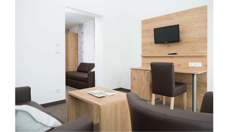 Tisch mit Stuhl, Fernseher an der Wand seitlich
