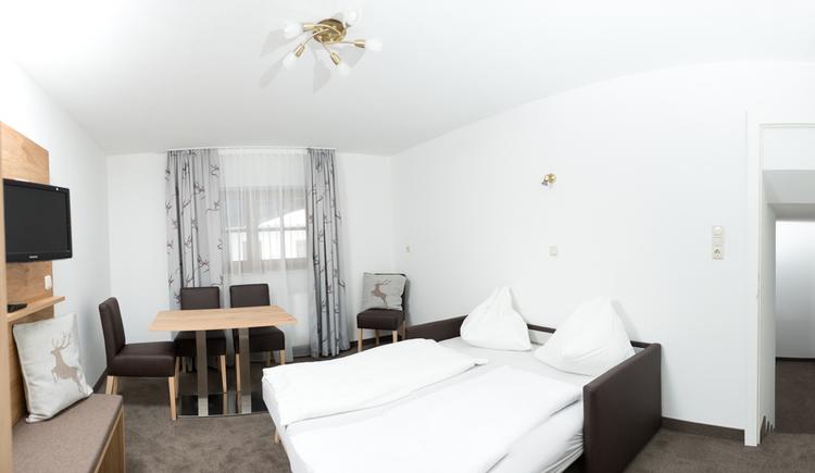Doppelbett, im Hintergrund Tisch mit Stühlen, Fenster, Fernseher an der Wand
