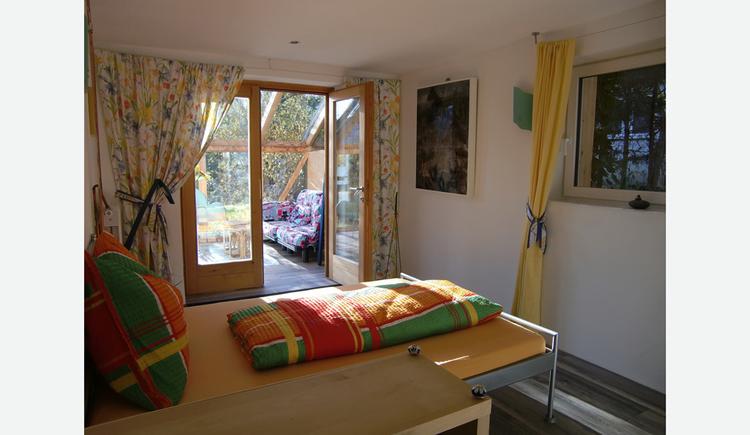 Bett, im Hintergrund seitlich offene Balkontür mit Blick in den Wintergarten, seitlich ein Fenster