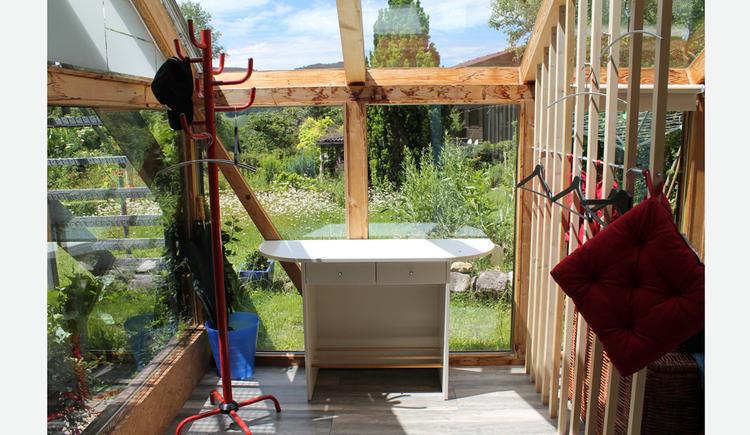 im Hintergrund ein Tisch, Blick durch die Glaselemente in den Garten