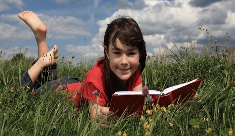 Kind liegt mit einem Buch in der Wiese