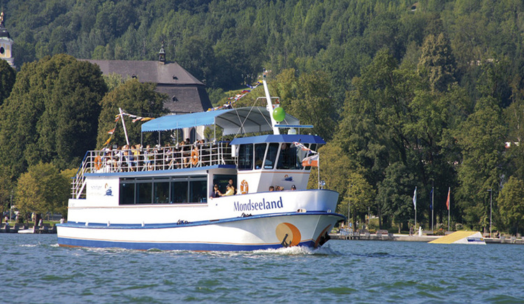 Panorama ship on the Mondsee in the background the Basilica St. Michael hidden behind the trees.