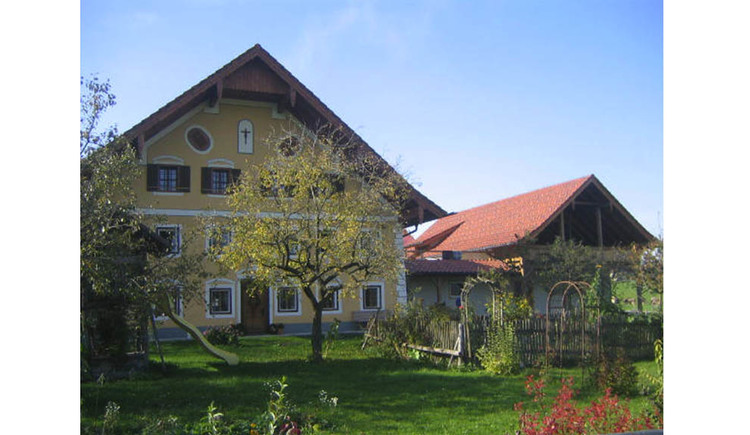 View of the house, in the front the garden, trees, meadow, slide. (© Strobl)