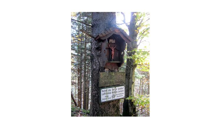 Blick auf das Baumkreuz, darunter Schilder, im Hintergrund ein Wald