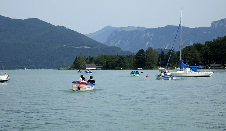 Some boats on a lake, in the background mountains