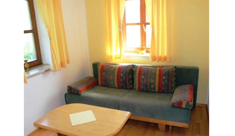 Couch mit Tisch, im Hintergrund Fenster