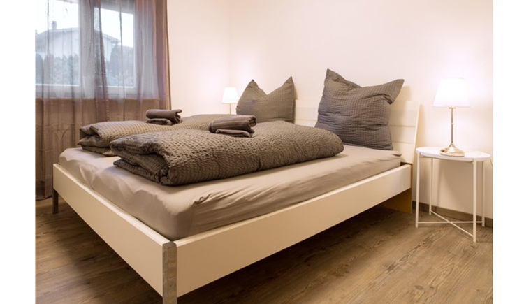 Schlafzimmer mit Doppelbett, kleiner Tisch mit Stehlampe