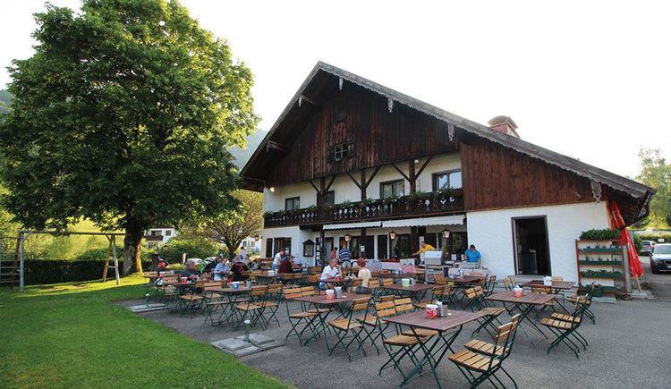Gastgarten, mit Stühlen und Tischen, auf denen einige Besucher sitzen, im Hintergrund der Gasthof und ein Baum. (© Gasthof Fohlenhof)