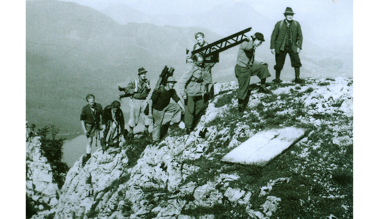 Personen transportieren ein Kreuz auf den Gipfel