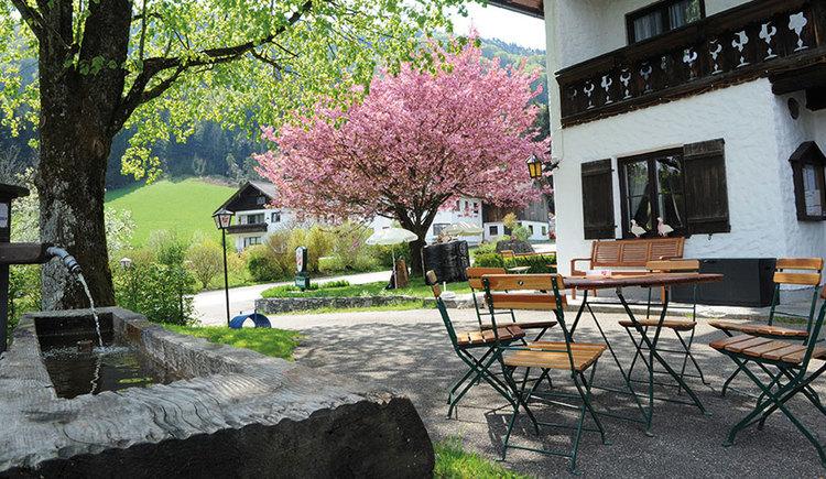 Blick in den Gastgarten mit Stühlen und Tisch, im Vordergrund ist ein Holzbrunnen zu sehen. (© Gasthof Fohlenhof)