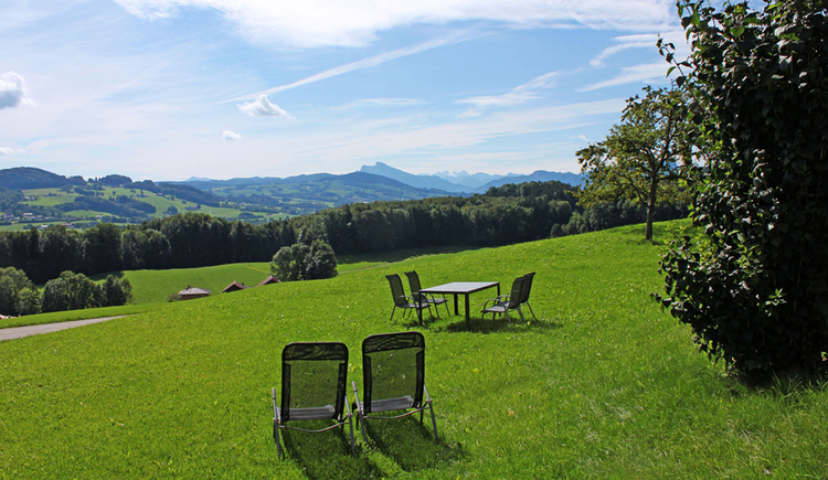 View of the countryside, sun loungers, table and chairs stand in the meadow, in the background forest and mountains