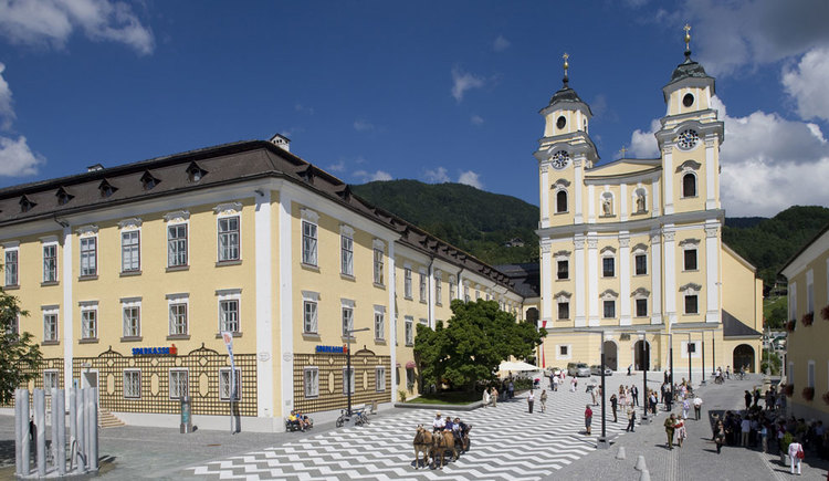 View over the Church square to the basilica St. Michael. You can also see a horse-drawn carriage and a fountain. (© www.mondsee.at)