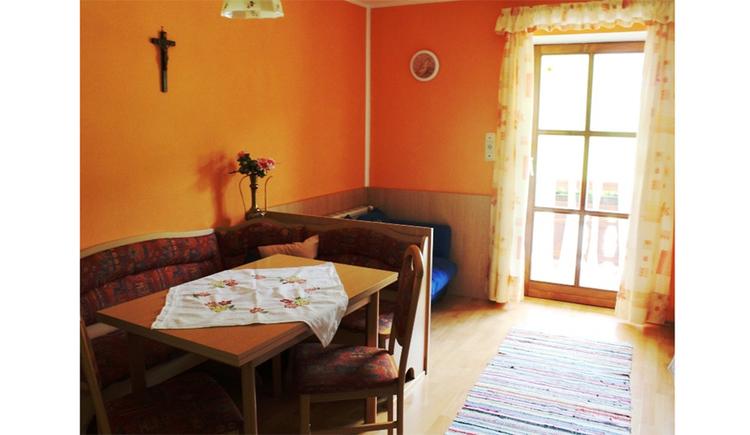 Wohnbereich mit Eckbank Tisch und Stuhl, im Hintergrund eine Balkontür