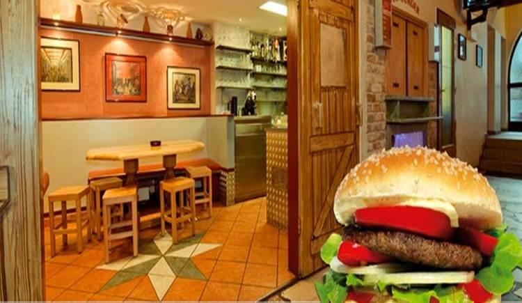 Innenbereich mit Tischen und Stühlen, im Vordergrund ein typischer Moonlake Burger. (© www.mondsee.at)