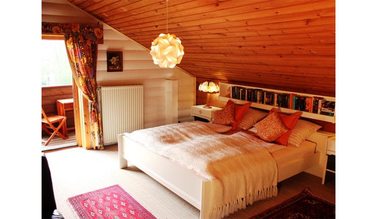 Schlafzimmer mit Doppelbett, Nachtkästchen, im Hintergrund Blick durch die offene Balkontür