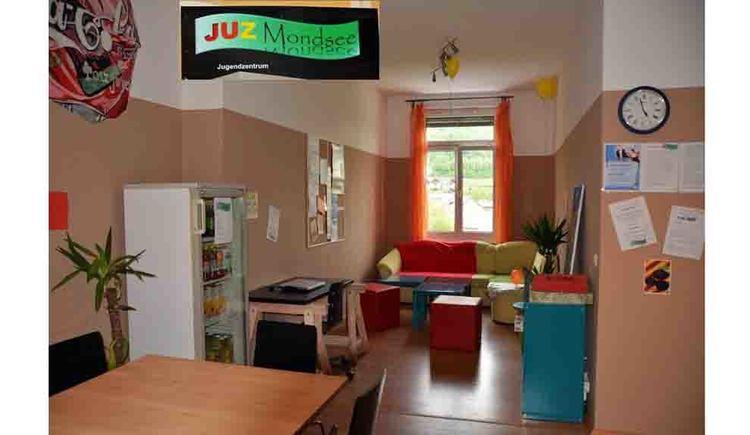 Tagesraum mit Kühlschrank, Couch, Fenster und Tisch