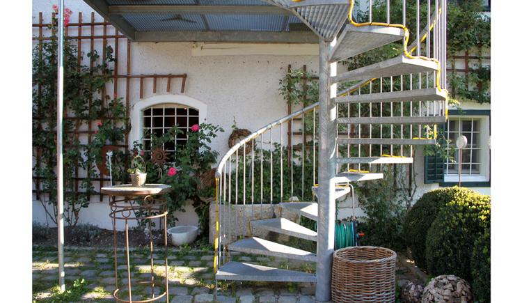 Blick in den Innenhof mit Wendeltreppe, an der Hausmauer Rosen