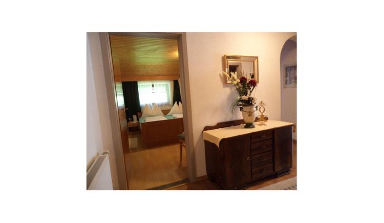 Blick vom Gang mit einer Kommode in das Schlafzimmer mit Doppelbett und Fenster
