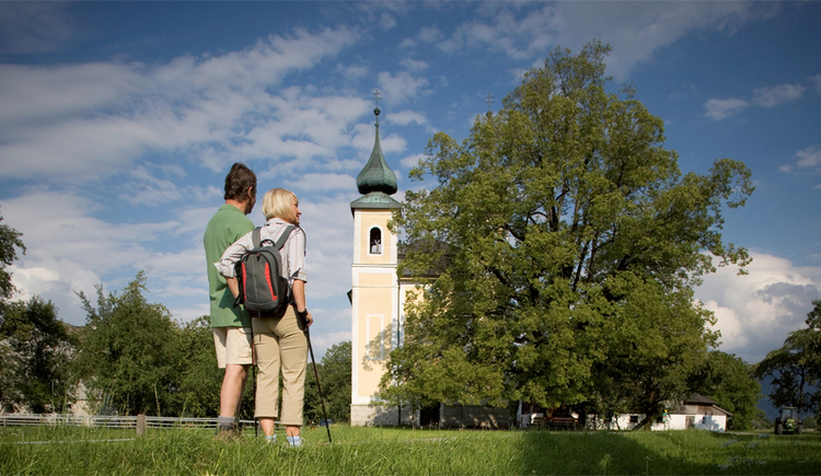 Wanderer stehen vor der Kirche, Baum. (© Tourismusverband MondSeeLand)