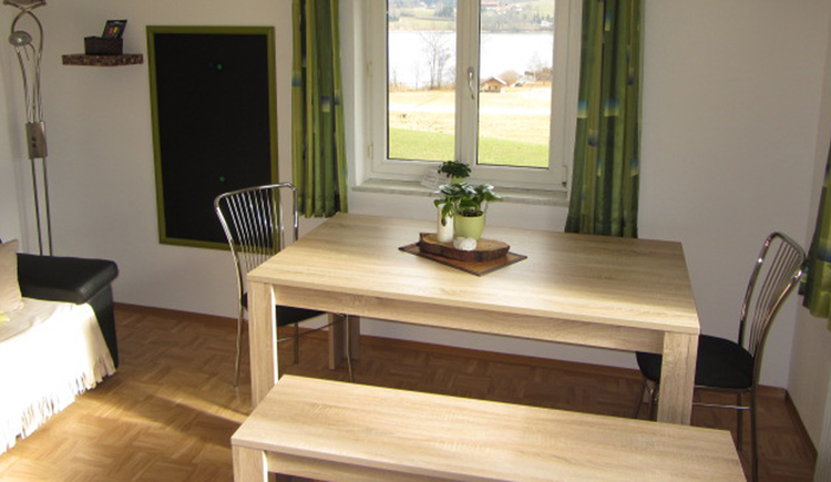 Dining room with a table, chairs and a bench. In the background a window with a view on the lake is visible.