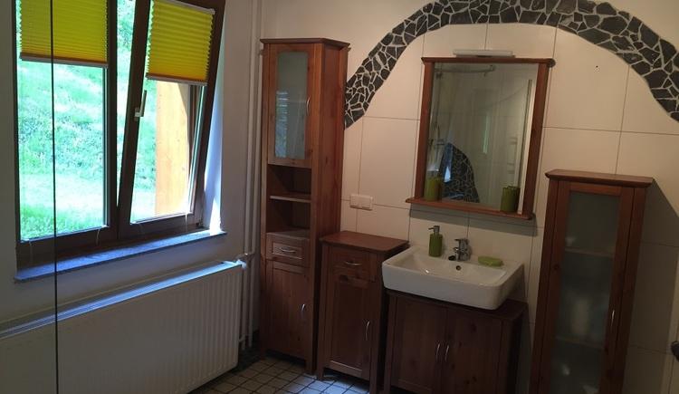Badezimmer mit einem großen Fenster und Badezimmerkästen für genügend Stauraum.