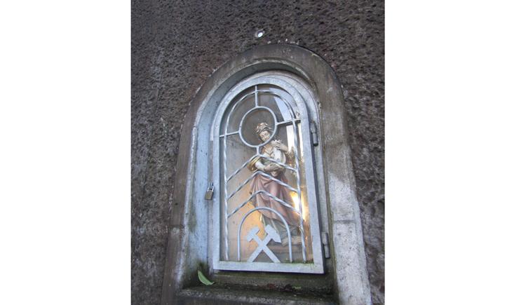 Blick auf eine Heiligenfigur hinter Gitter
