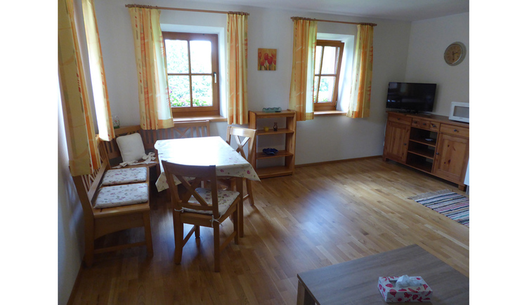living area with on the left and in the background the dinette, two benches, table and two chairs, wooden floor, three Windows and on the right a shelf with the TV and a carpet on the wooden floor, in front the little table