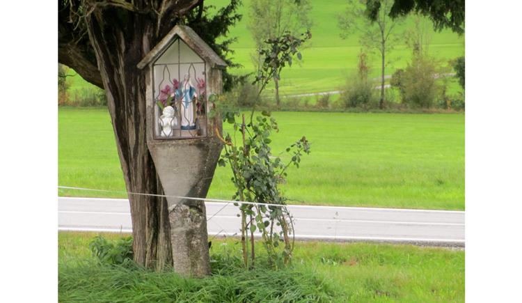 Blick auf einem Bildstock bei einem Baum, im Hintergrund Wiesen, Sträucher