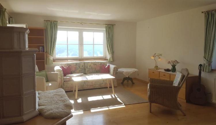 seitlich ein Kachelofen, im Hintergrund Sofa, Tisch, Fenster, seitlich eine Kommode, Stuhl