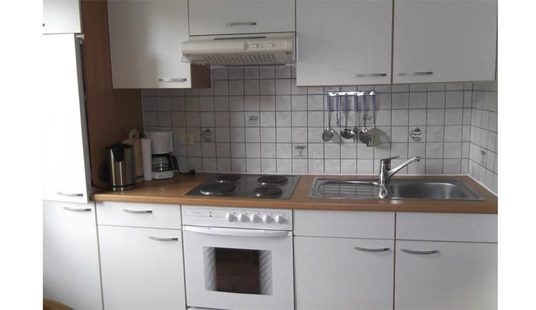Küche mit Ofen, Abwasch, Kaffeemaschine, Wasserkocher, verschiedene Küchenutensilien hängen an den Fliesen