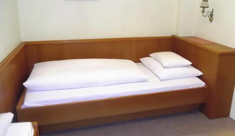 Schlafzimmer mit Einzelbett, Lampe an der Wand seitlich, Teppichboden