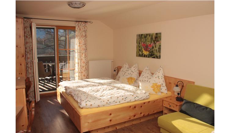 Doppelbett, Sofa, im Hintergrund eine Balkontür