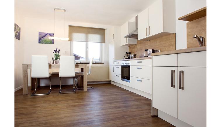 seitlich eine Küche, im Hintergrund Tisch und Stühle, Fenster