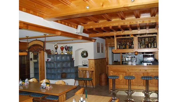 Gaststube mit Bar, Barhocker, im Hintergrund ein Kachelofen, Tisch, Stühle