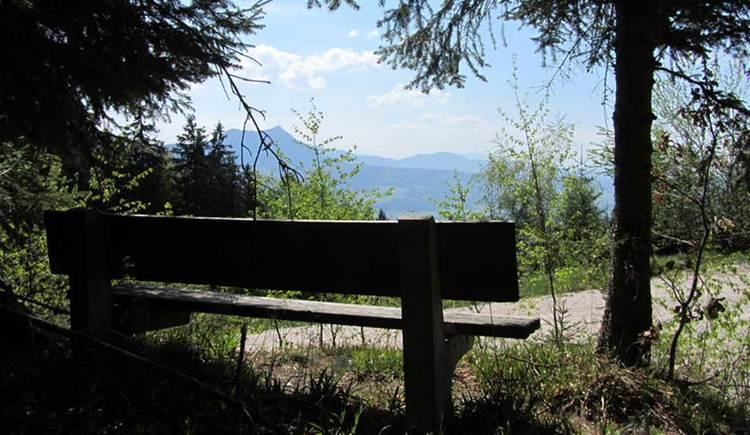 Aussichtsbank am Weg- und Waldrand mit Blick über das MondSeeLand, im Hintergrund die Berge