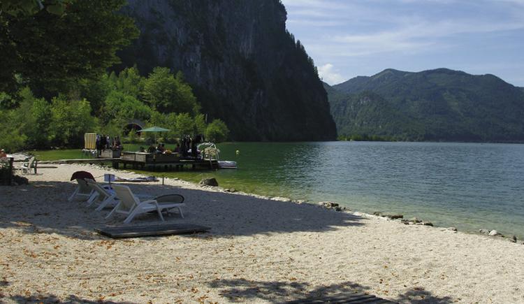 Badeplatz mit Liegen, im Hintergrund der See und die Berge