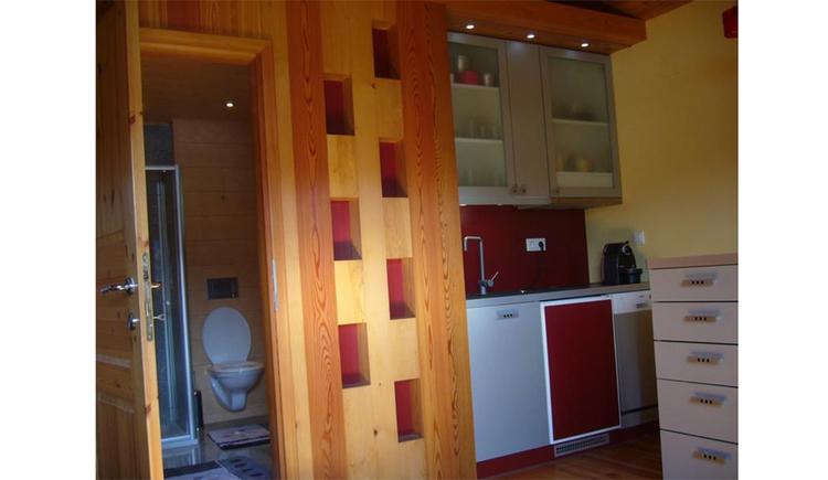 Wohnbereich mit Küchenblock, Kaffeemaschine, Blick durch die offenen Tür ins Badezimmer mit Toilette und Dusche